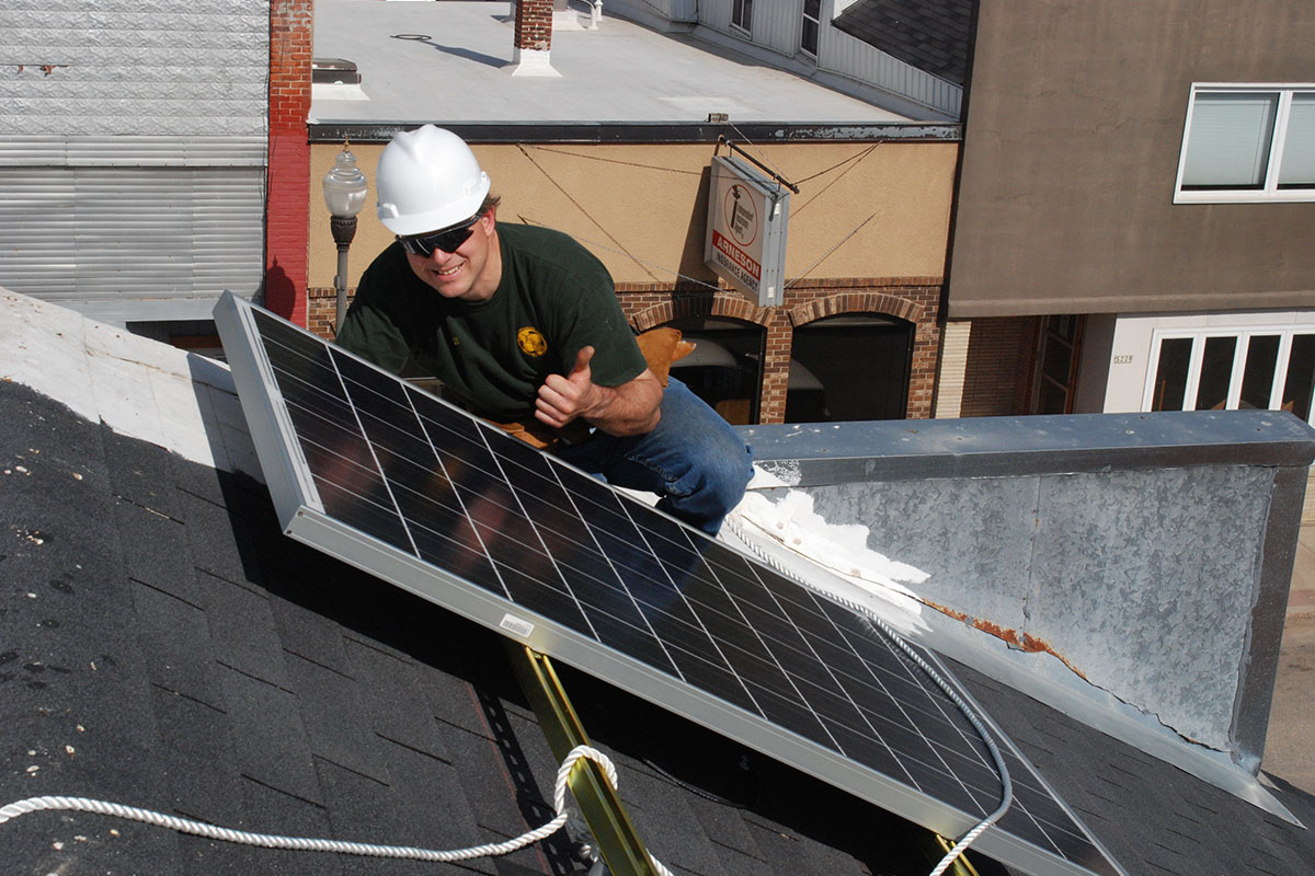 solar installer in a white hard hat giving a thumbs up on a roof with a solar panel